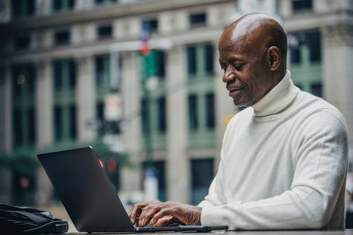 Side view of self employed concentrated mature bald black man in stylish turtleneck sitting in street cafe and typing on netbook during work