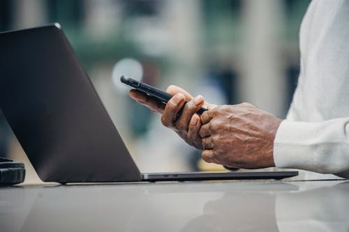 Crop anonymous elderly black businessman in casual outfit messaging on smartphone while sitting in street cafe during remote work on laptop