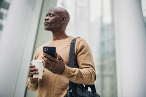 Serious black man browsing phone while standing on street with takeaway coffee