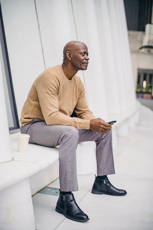 Side view of confident bald mature black male entrepreneur in stylish outfit browsing mobile phone while having coffee break on city bench