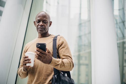 Focused mature black man chatting on smartphone during coffee break on street