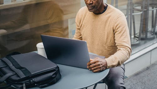 Crop thoughtful black man working on netbook in street cafeteria