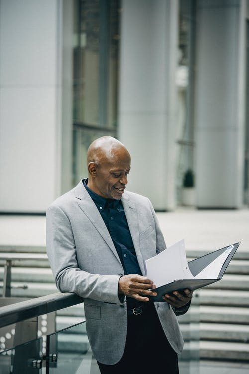 Content middle aged African American male manager in formal suit smiling while checking documents standing near modern building