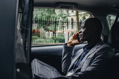 Side view of thoughtful mature African American businessman in elegant suit talking on smartphone while riding on passenger seat of taxi