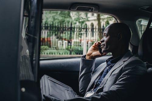 車に座ってスマートフォンで話す物思いにふける黒人男性