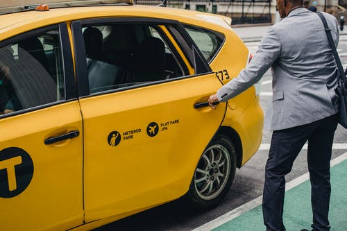 Anonymous elegant black man getting into taxi on street