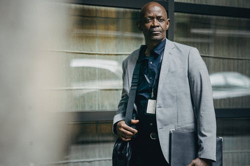 Serious black businessman with bag standing near building wall