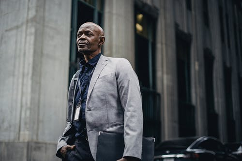 Confident black businessman standing against modern building in urban street