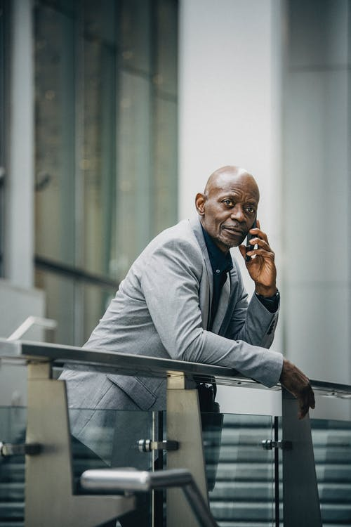 Side view content adult African American businessman in formal wear leaning on glass railing near contemporary business center and having conversation on mobile phone while looking away