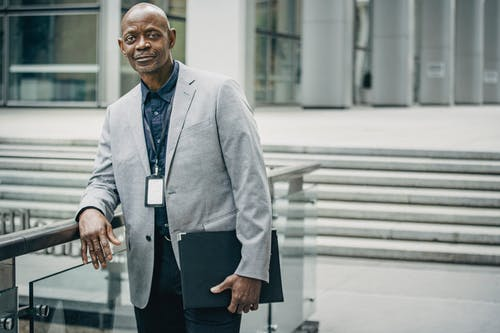Positive black businessman leaning on railing near modern business center