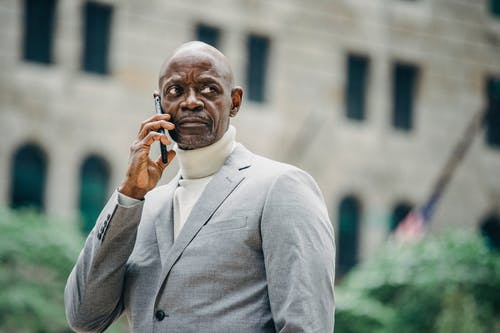 Serious black businessman talking on smartphone on street