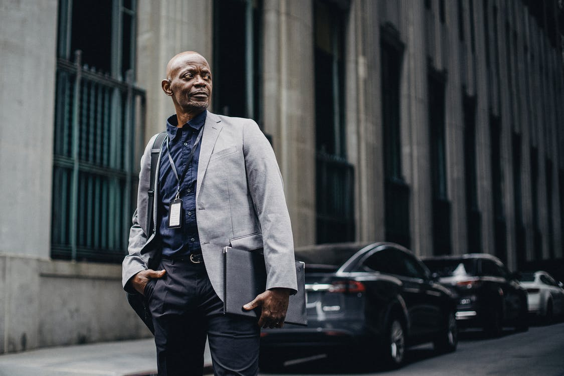 Serious adult African American businessman in formal suit standing with hand in pocket on urban street and looking away thoughtfully
