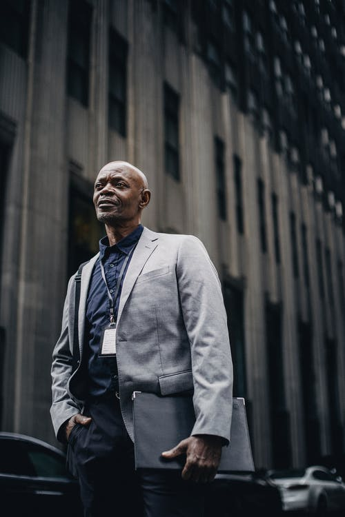 Respectable black businessman standing on city street
