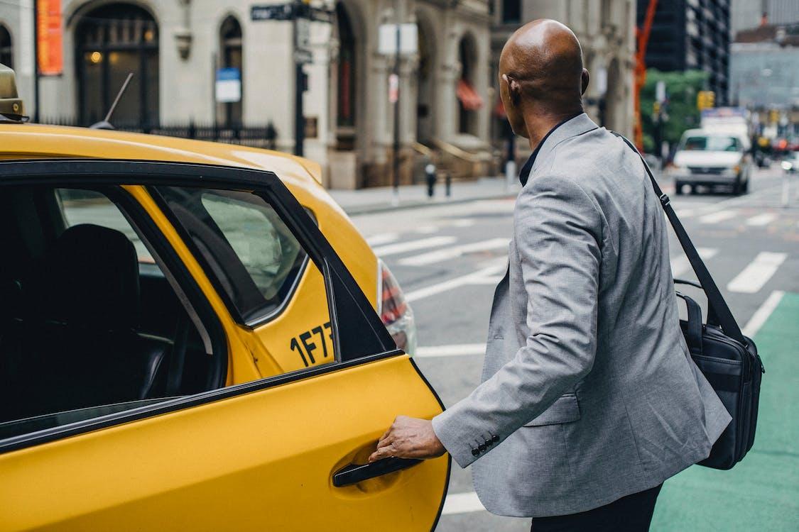 Faceless black man opening taxi door on busy street