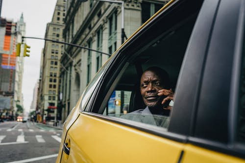 Man Sitting By The Window Of A Yellow Car