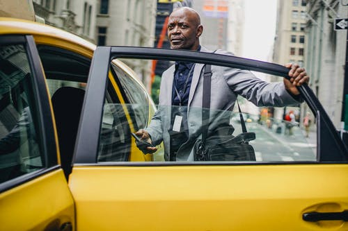 Black businessman opening taxi door in modern city