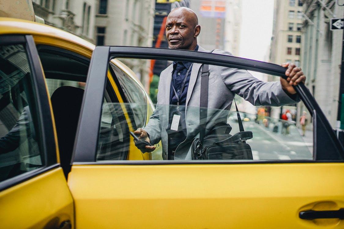 Black businessman opening taxi door in modern city
