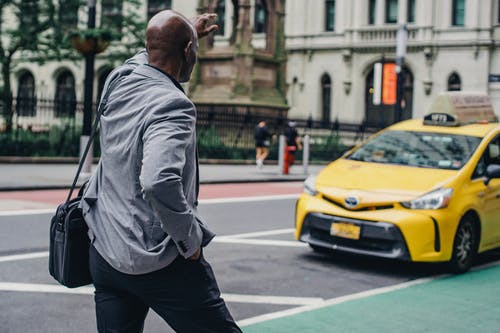 Unrecognizable black man catching taxi on city road