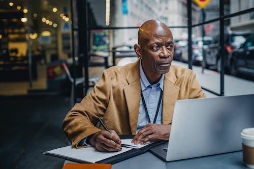 Gerente Negro Pensativo Con Laptop Y Papeles En Cafe