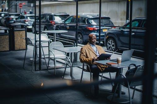 Trabajador De Oficina étnica Concentrada Con Carpeta Y Portátil En La Cafetería