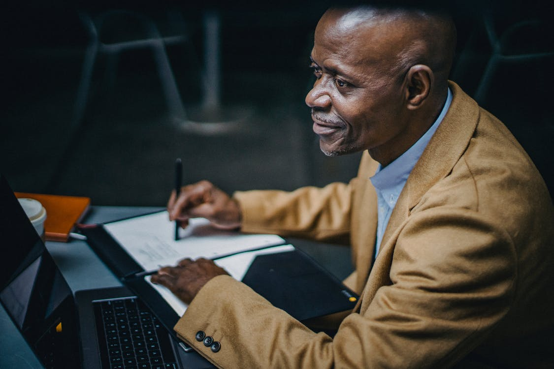 From above side view of crop content mature ethnic male executive with netbook looking away at cafeteria table