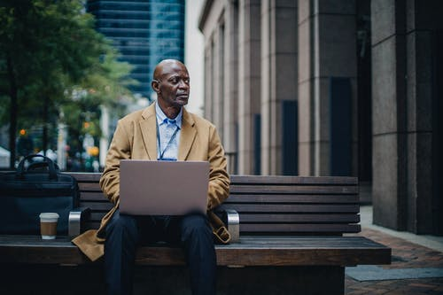 Serious black male executive with laptop on street bench