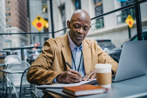 Oficinista Masculino Negro Escribiendo En Papel Cerca De La Computadora Portátil En El Interior