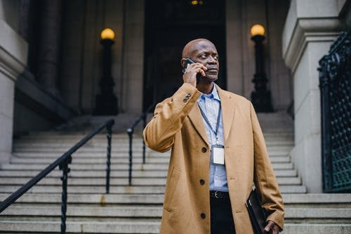 Contemplative black office worker conversing on smartphone on street staircase