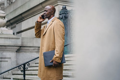 Side view of serious mature African American male entrepreneur with folder speaking on cellphone on urban staircase while looking forward