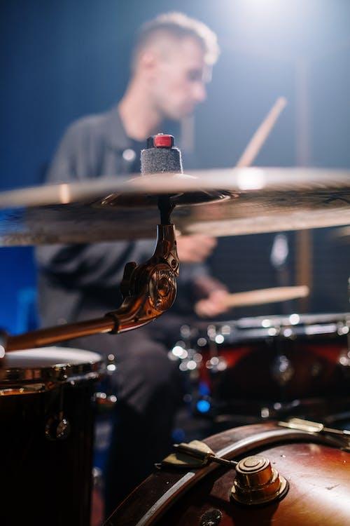 Man in White Shirt Playing Drum