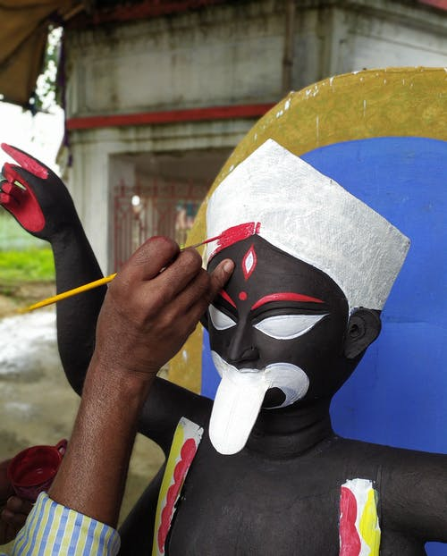 Person Holding White Red Blue and Yellow Mask