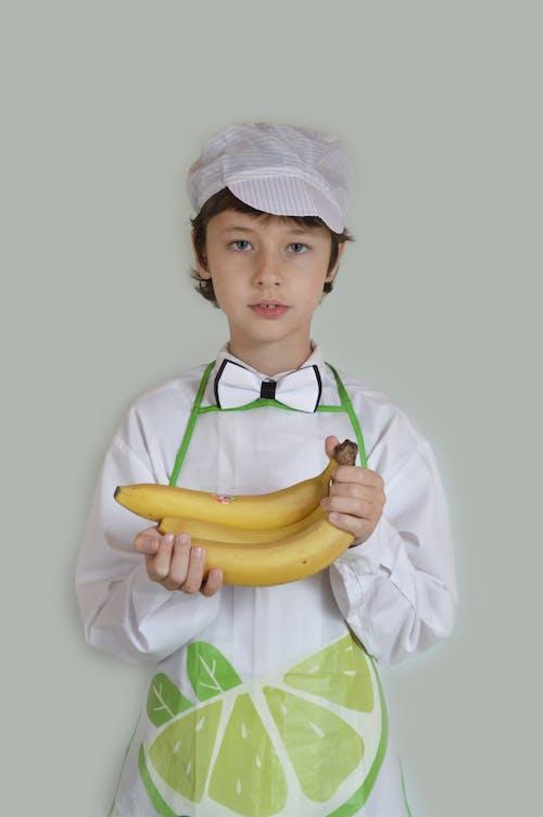 Boy chef showing ripe bananas in studio