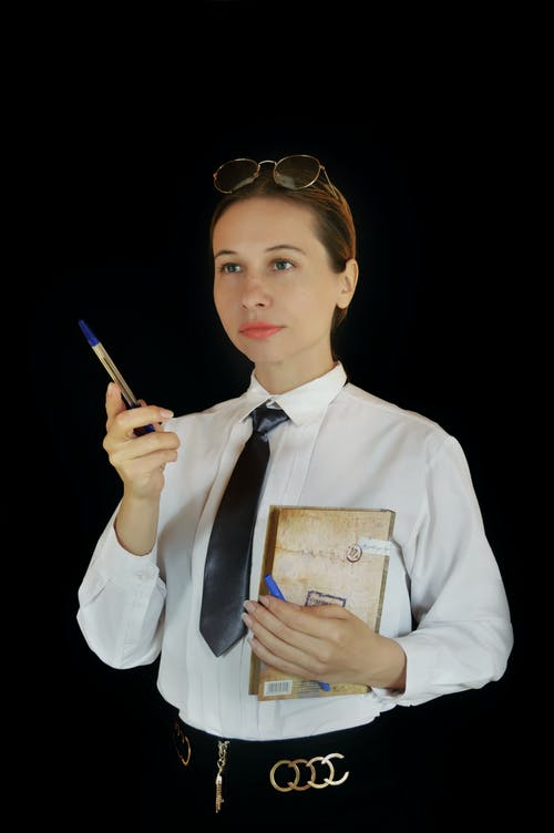 Focused businesswoman standing with diary in studio