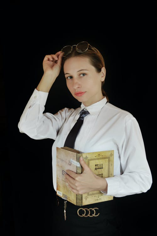 Young businesswoman with diary putting on eyeglasses in studio