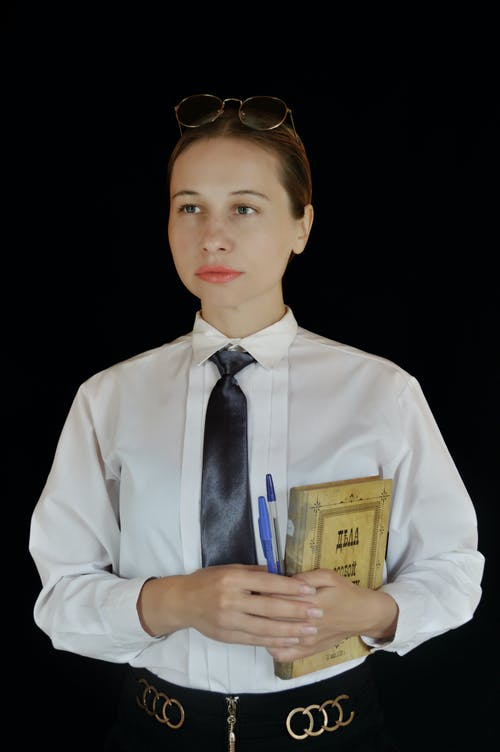 Young businesswoman standing with notepad in studio