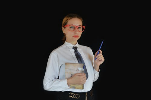 Clever young female executive in formal clothes and eyeglasses standing with diary and pen on black background and looking at camera thoughtfully