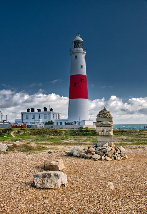 White and Red Lighthouse Under Blue Sky