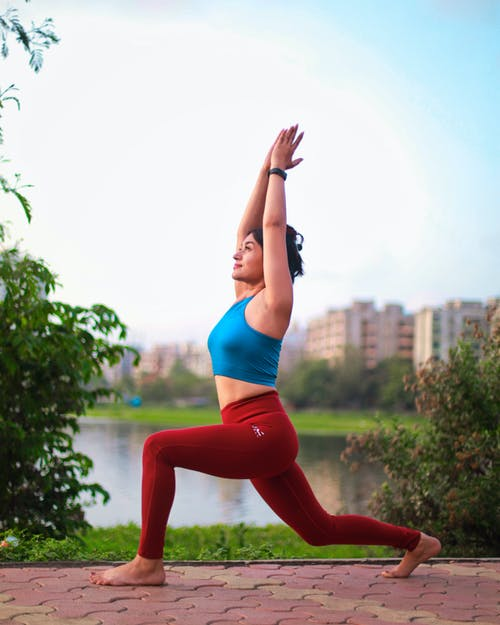Woman in Blue Sports Bra and Red Leggings Doing Yoga Pose