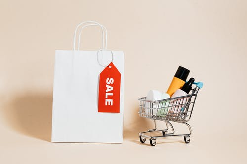A White Paper Bag and Shopping Cart on Beige Background