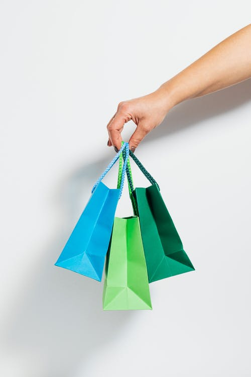 Hand Holding Three Shopping Bags