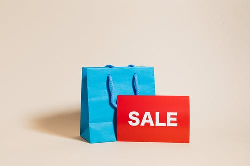 Blue Shopping Bag and a Red Sale Sign
