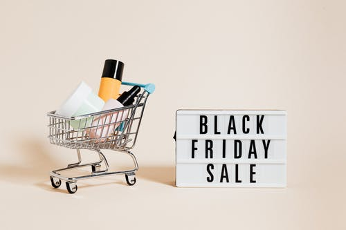 Products in a Shopping Cart Beside a Black Friday Sale Signage on Beige Background