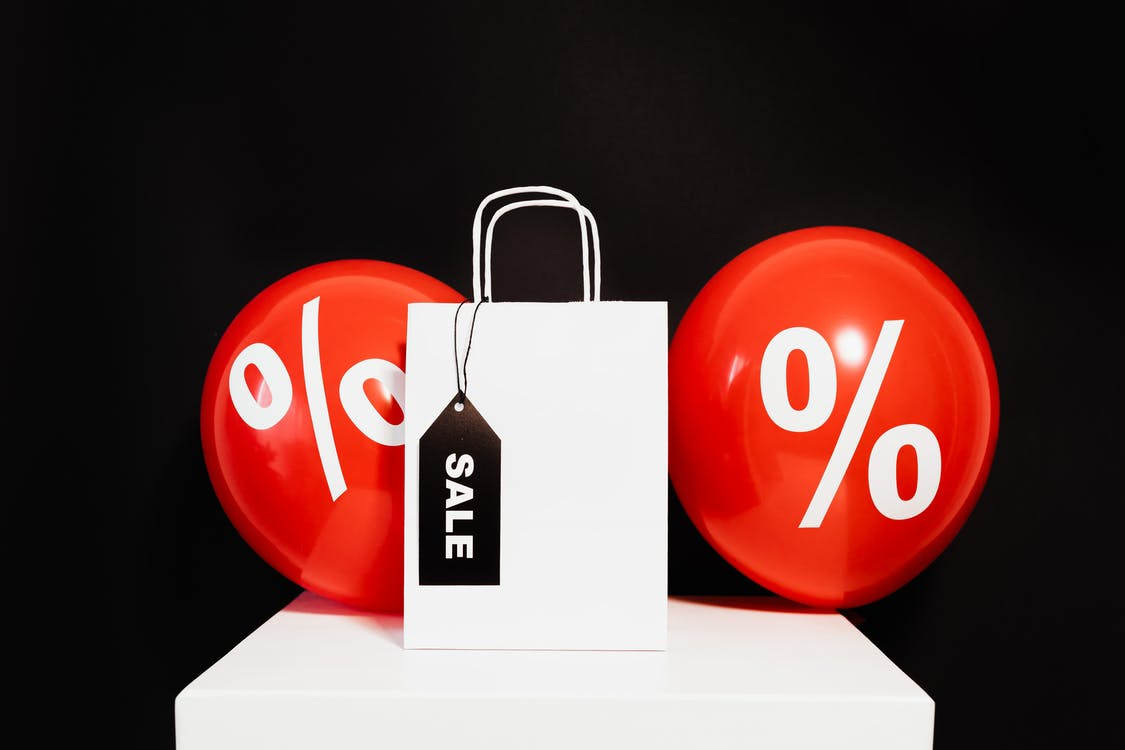 A White Paper Bag in Between Red Balloons With Percentage Symbol on a Black Background