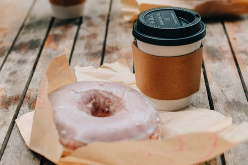 Tasty sweet chocolate donut and takeaway cup of coffee placed on wooden surface in daytime