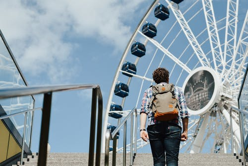 Woman in Brown and White Floral Shirt and Blue Denim Jeans Standing Near Ferris Wheel during