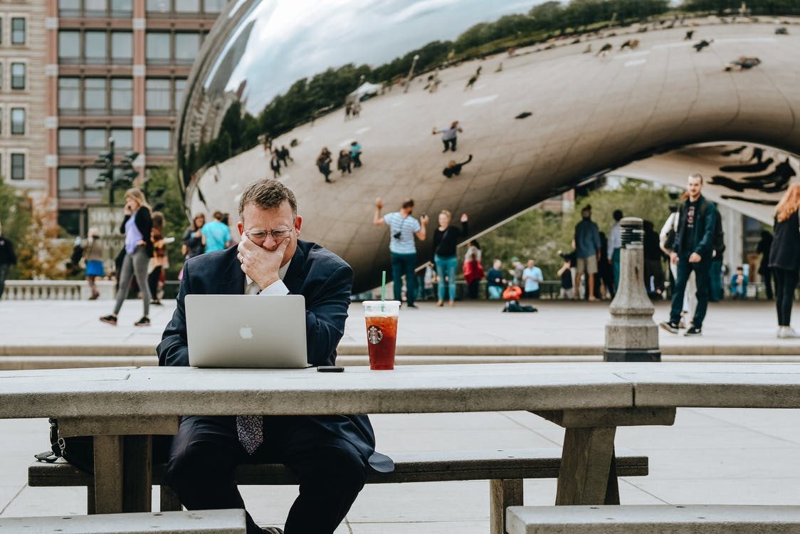 Concentrated businessman in suit touching face and sitting at table with laptop and takeaway drink against modern art sculpture Cloud Gate in Chicago in daytime