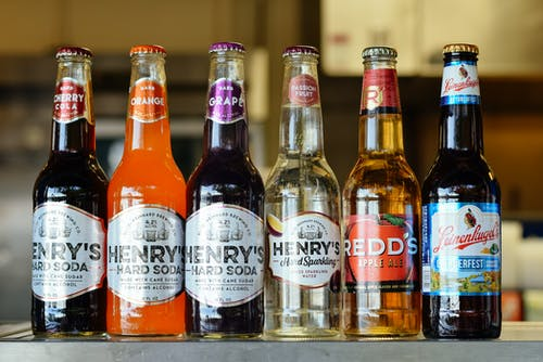 Six Assorted Label Bottles on Brown Wooden Table