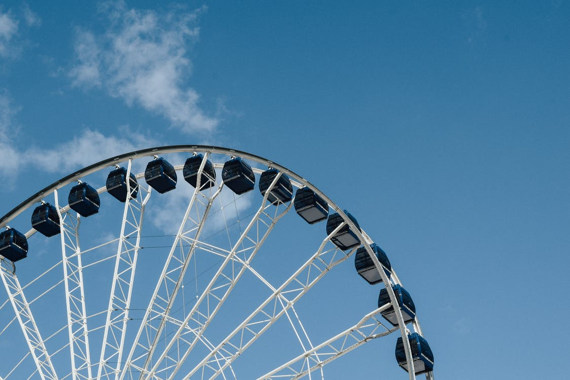 From below of contemporary observation wheel located in city against blue sky in daytime