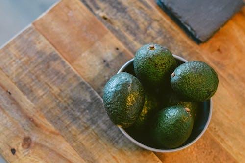 Green Round Fruits on Black Ceramic Bowl