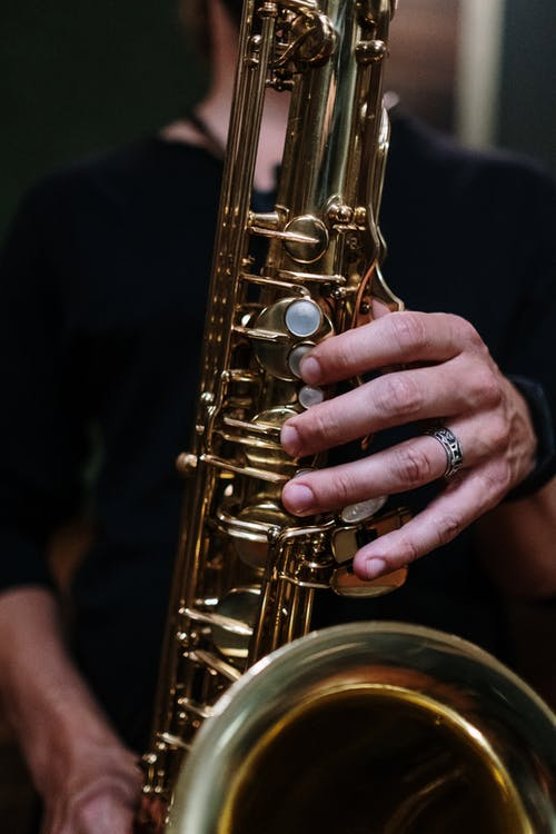 Person Holding Brass Saxophone